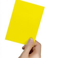 Gelbe Karte in einer Hand